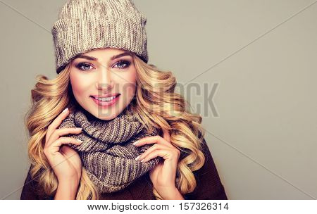 trendy warm winter - beautiful  young blonde  woman in gray wool winter hat and scarf smiling .  Portrait of beauty  winter girl  in knitted  woolen  clothing hat and  Snood .