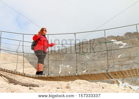 Mountaineer woman walking over a chain bridge (klettersteig) over gorge to Zugspitze peak in Alps. Germany Austria border.