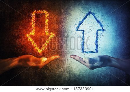 Two human hands holding flaming and splashing infographic arrows on a gray background. Business situation growth and decline.