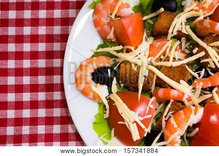 Caesar salad with shrimp, olives and croutons