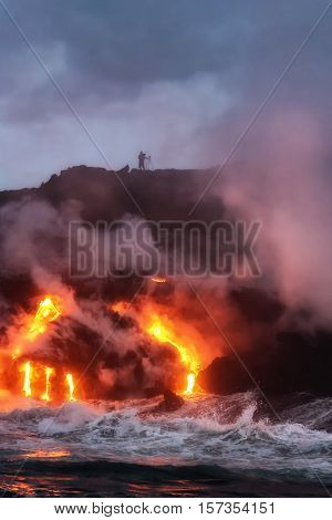 Molten lava flowing into the Pacific Ocean on Big Island of Hawaii as photographer watches on cliff top