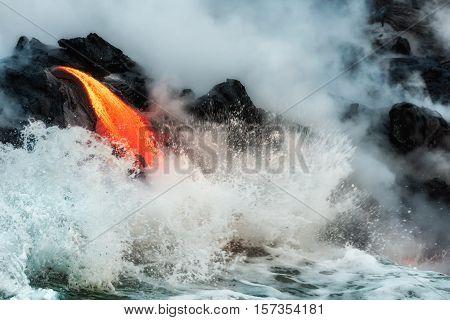 Waves crash onto molten lava flowing into Pacific Ocean on Big Island of Hawaii