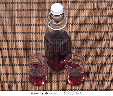 Homemade raspberry liqueur in clear glass bottle with swing top and shot glass on bamboo  placemat