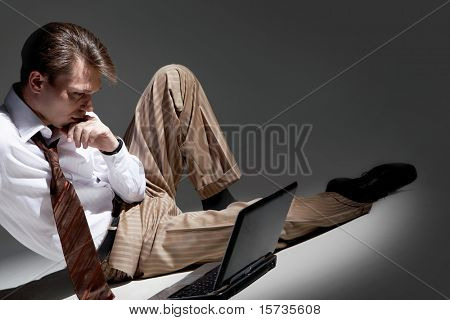 Photo of pensive businessman looking at laptop monitor and thinking of new idea
