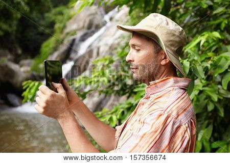 Nature, Ecology And Science Concept. Serious Biologist In Striped Shirt Holding Touch Pad, Taking Pi