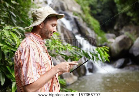 Bearded Botanist Wearing Panama Hat Using Digital Tablet Pointing At Blank Screen With Happy Express