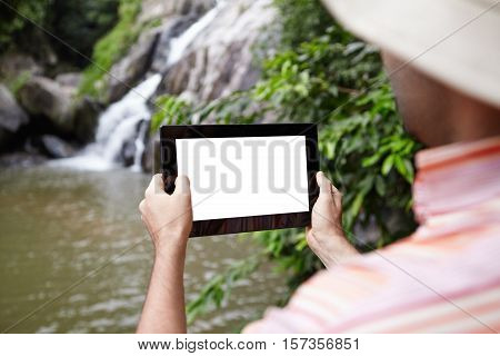 Rear View Of Biologist Wearing Panama Hat Taking Picture Of Mountain Waterfall In Nature Park Using