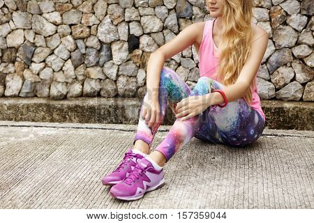 Cropped View Of Attractive Athletic Woman Sitting On Pavement Having Break During Jogging Workout Ou