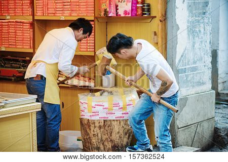 Chinese Men With Wooden Mallets Are Crushing Nuts, Lijiang