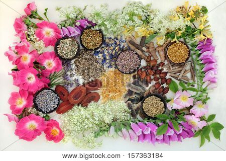 Natural alternative medicine selection of herbs and flowers in wooden bowls on hemp paper background. background.