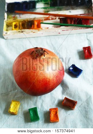 ripe red pomegranate with art aquarell paints and brushes still life on blue cloth