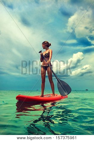 Young slim girl stand up on paddle Board in turquoise sea , SUP, Tropical Blue Ocean . Thailand ,water sports , active lifestyle
