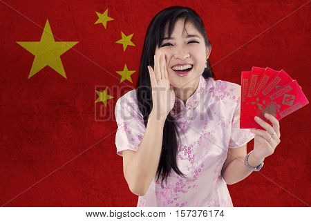 Picture of beautiful chinese girl wearing cheongsam clothes while holding red envelope and yelling at the camera with a Chinese flag background