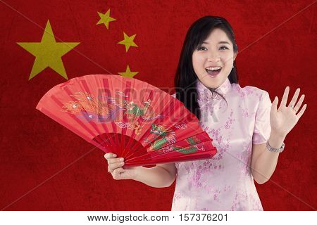 Picture of cheerful Chinese girl wearing cheongsam dress and holding a fan with Chinese flag background