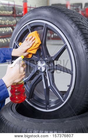 Close up of hand person is cleaning dust on a rim with cloth and spray in the workshop