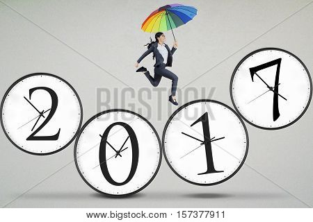Photo of an optimistic business woman jumping on the number 2017 while holding an umbrella. Concept of chasing a dream and success in 2017