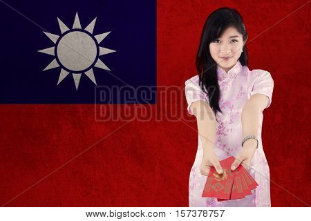 Image of pretty young woman showing red envelope while wearing cheongsam dress with flag of Taiwan