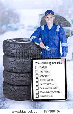 Young technician leaning with a stack of tires while holding wrench and information about winter driving on the board