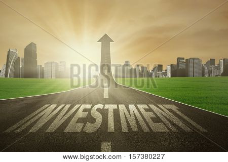 Road with Investment word turning into an arrow rising upward symbolizing the way to improve investment