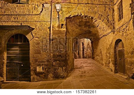 Pitigliano, Grosseto, Tuscany, Italy: picturesque old alley and underpass at night in the medieval village founded in Etruscan time
