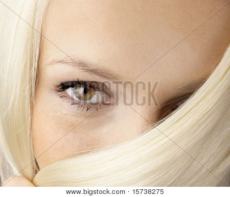 fresh look - beautiful brown eye poping out of the blond hair. woman face
