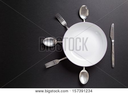 White plate with cutlery over black background.Userful as background for food restaurant menu or other