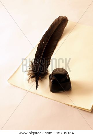 feather quill and inkwell over paper