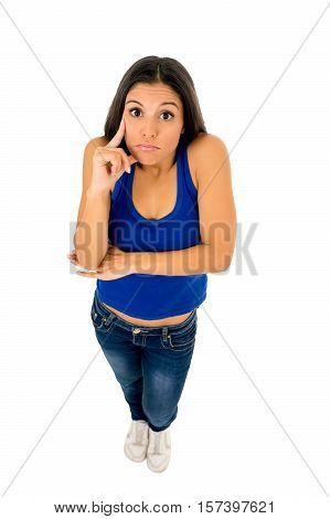 young attractive hispanic woman in casual top and jeans shrinking shoulders pointing her head thinking and wondering confused in doubt isolated on white background