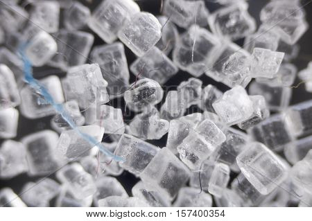 White sugar crystals with a blue thread.