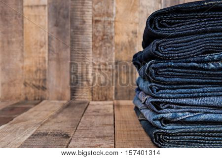 Stack of blue jeans on old wood background with copy space