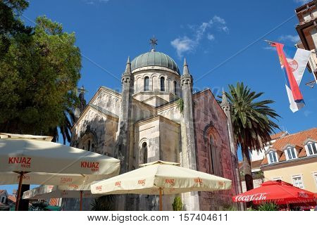 HERCEG NOVI, MONTENEGRO - JULY 18, 2016: St. Archangel Michael Orthodox Church surrounded by umbrellas of cafes and bars in Old Town