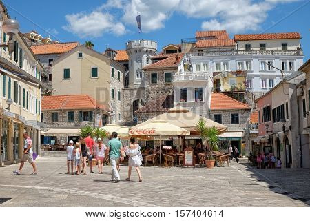 HERCEG NOVI, MONTENEGRO - JULY 18, 2016: the old town gate with the small clocktower surrounded by old houses, cafes and bars