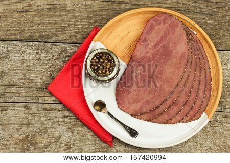 Cold roast beef on a wooden table. Delicacy of beef. Preparing cold refreshments. Traditional meal. Beef roast beef with green pepper.