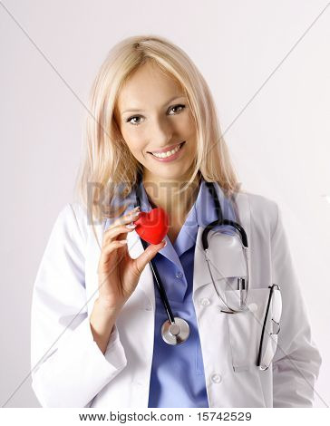 cardiologist, Beautiful young doctor with stethoscope and human heart in hand