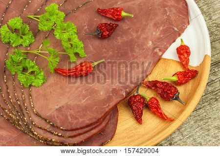 Cold roast beef on a wooden table. Delicacy of beef. Preparing cold refreshments. Traditional meal. Beef roast beef with green pepper and chili peppers.