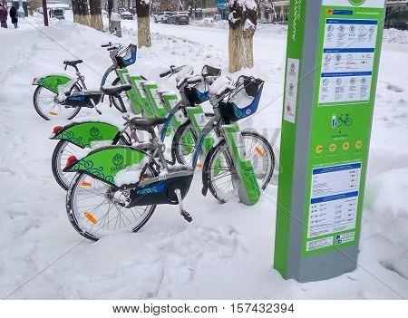 ALMATY KAZAKHSTAN - November 20 2016: The automated station rental bike under the snow in the city of Almaty Kazakhstan