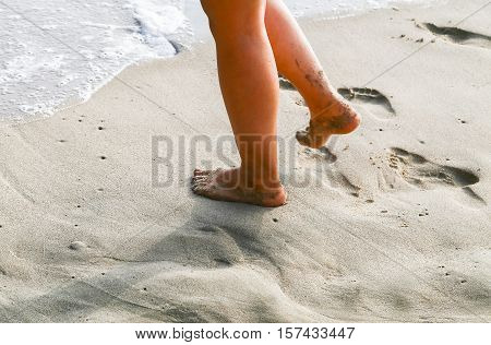 Close-up of feet walking on the beach at Santa Monica USA leaving footprints in the wet sand.