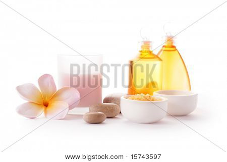 Bottles of SPA cosmetic products and bath salt, pebbles and frangipani flowers on white background