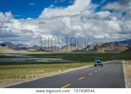 Car driving on the paved mountain road from Ali to Lhasa through the high central Tibetan plateau, Tibet, China