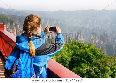 Female Tourist With Smartphone Taking Photo Of Mountains
