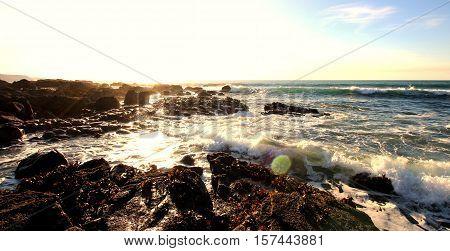 Glistening sun bathed rocky Cornish coatline with waves crashing over rocks.