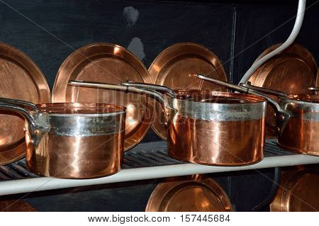 antique copper pans in row  resting on shelf
