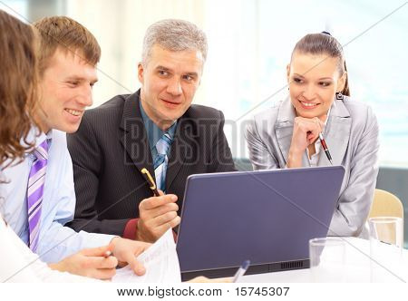Small business team in the office in front of a whiteboard discussing a project