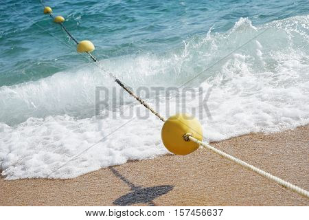Yellow buoy with rope on sand beach