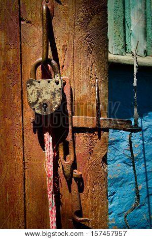 Old padlock on the barn door texture background. Kharkov region, Ukraine.