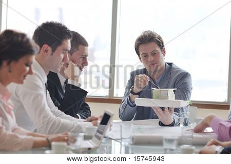 Grupo da equipe do negócio do arquiteto pessoas na reunião, procurando o modelo e concepção da nova casa imóveis