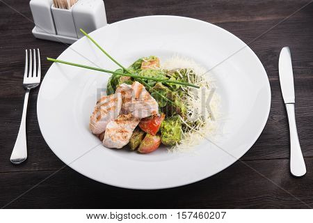 caesar salad with chicken tomato and chesse on white plate