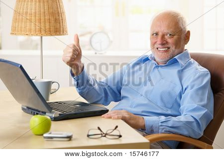 Happy senior man giving thumb up, sitting at desk using laptop computer at home.?