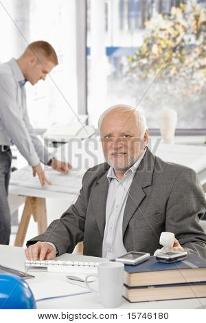 Portrait of senior architect in office, young designer working in background.?
