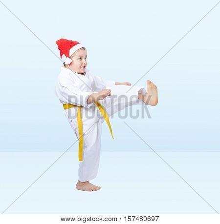 In karategi boy beats kicking on the light background